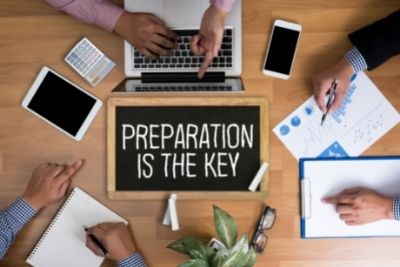 people round desk sign saying preparation is key
